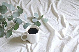 På bordet med den hvide dug står en kop friskbrygget kaffe.