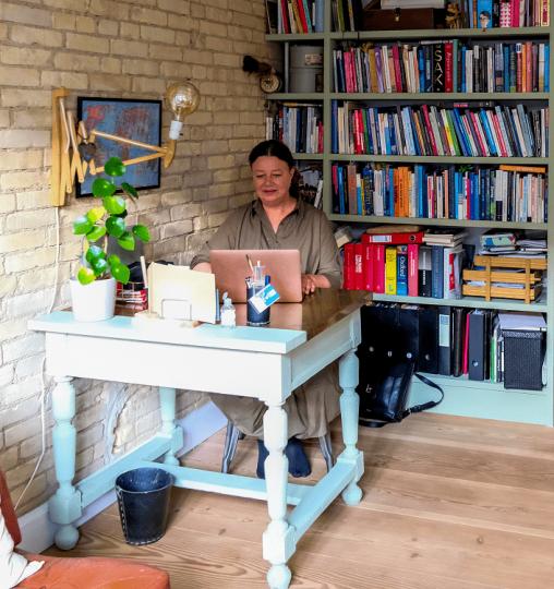 Mie Sidenius Brøner sidder og skriver på computer ved sit turkise vintage skrivebord i klinik Coeur.
